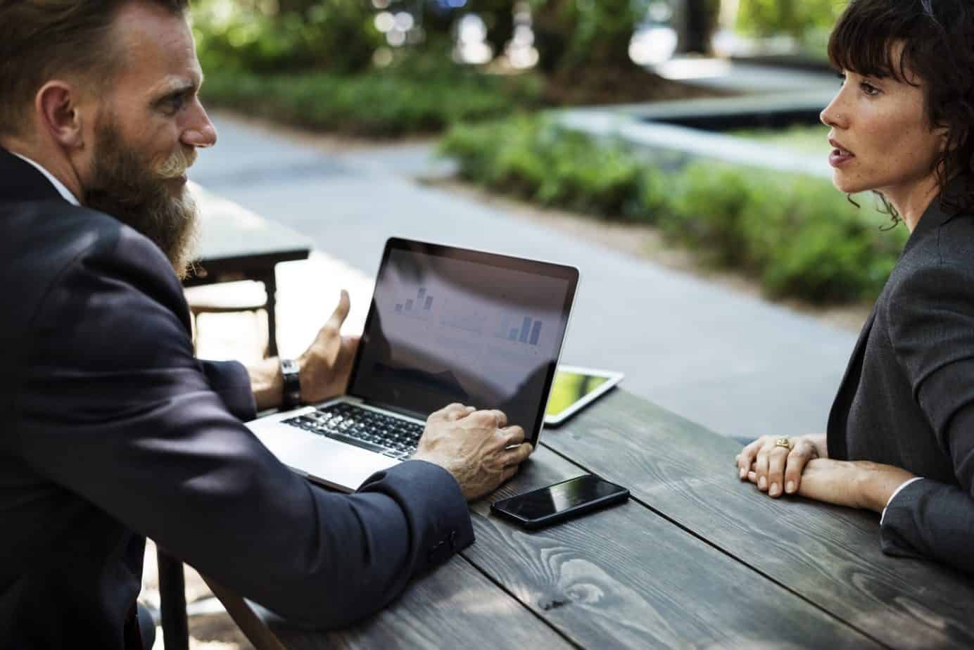 Man on a laptop talking to a woman